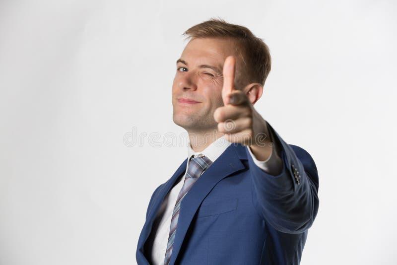 Affärsman som blinkar och pekar till kameran arkivfoton