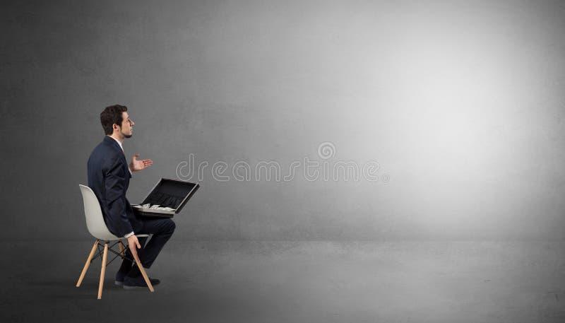 Affärsman som blir i ett tomt rum med material på hans varv arkivbild