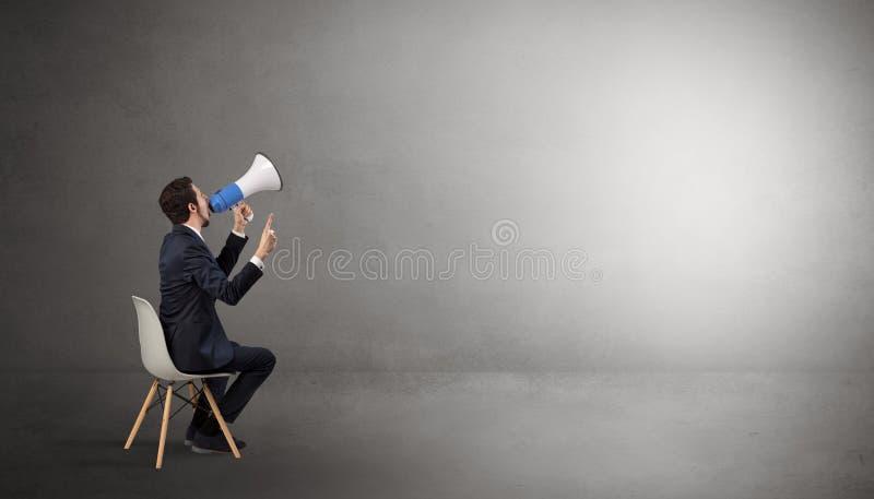 Affärsman som blir i ett tomt rum med material på hans varv arkivbilder