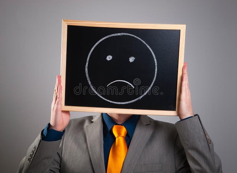 Affärsman som döljer hans framsida med en vit affischtavla med en ledsen fa arkivfoton