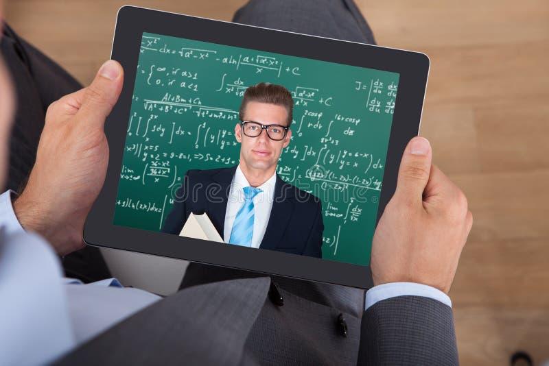 Affärsman som deltar i online-matematiks föreläsning på den digitala minnestavlan royaltyfri fotografi