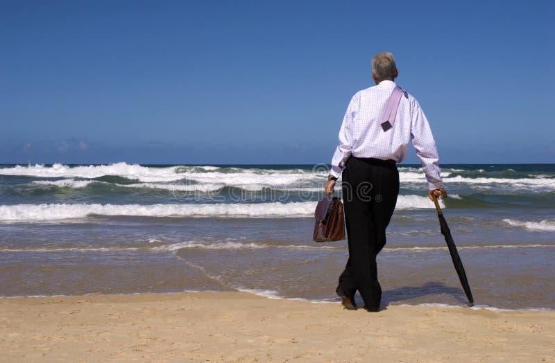 Affärsman som drömmer av avgångfrihet på en tropisk strand, kopieringsutrymme fotografering för bildbyråer