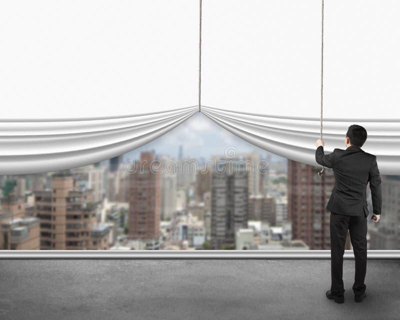Affärsman som drar den öppna tomma vita gardinen med siktsstadsbuil royaltyfria bilder