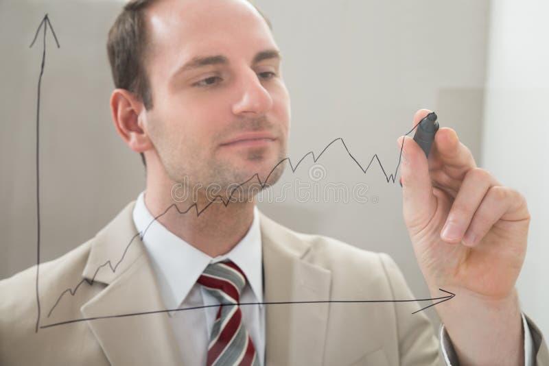Affärsman som drar en graf på en glass panel royaltyfria bilder