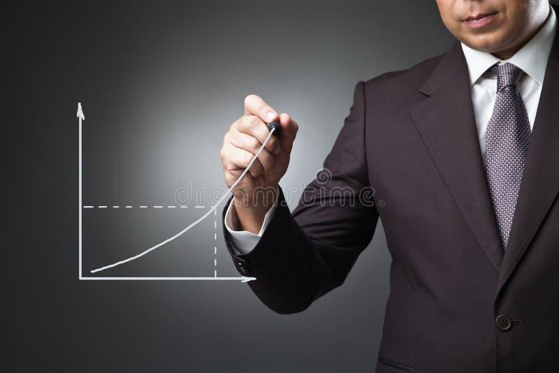 Affärsman som drar en växande graf royaltyfria bilder