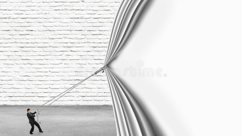 Affärsman som drar ner den tomma vita väggen för gardinbeläggningtegelsten royaltyfri foto