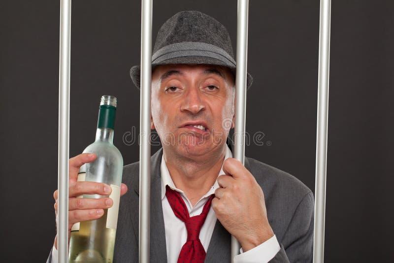 Affärsman som drickas i arrest royaltyfri fotografi