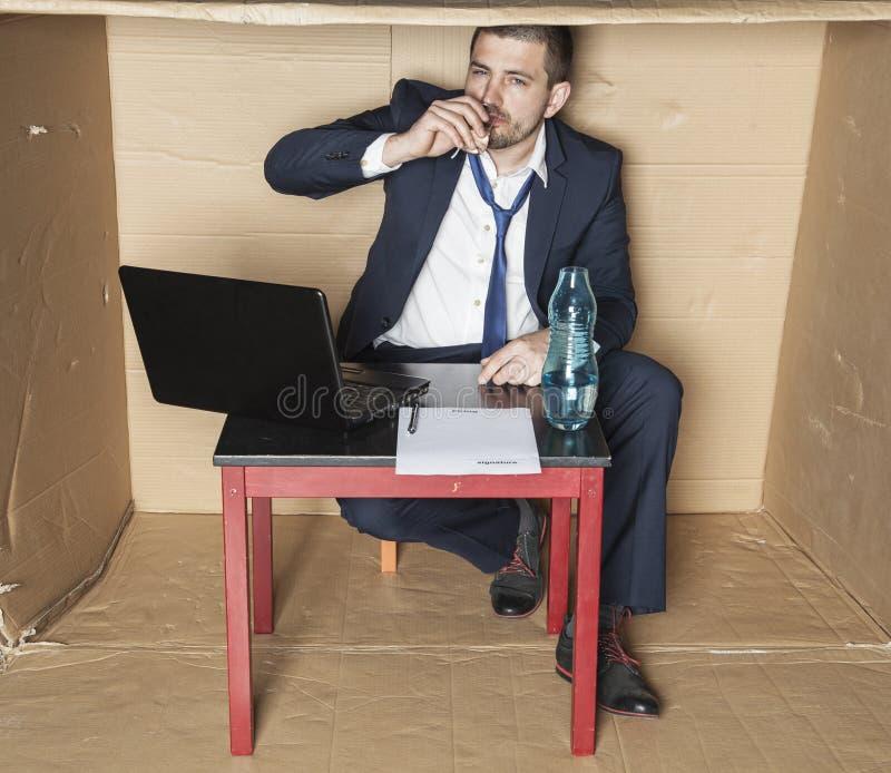 Affärsman som dricker alkohol under arbetstid arkivfoto