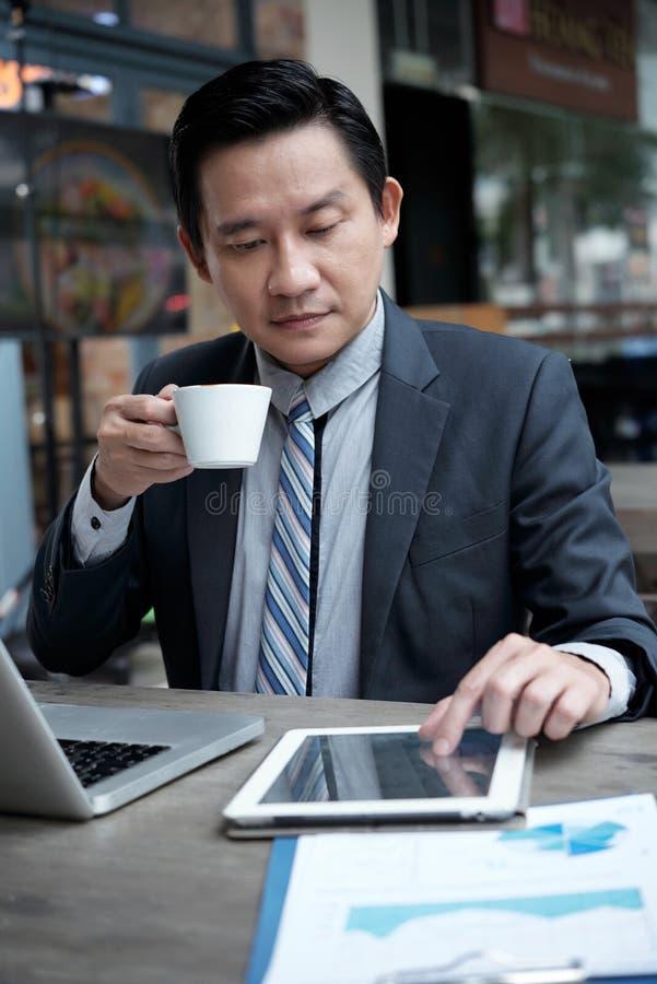Affärsman som dricker kaffe och direktanslutet läser nyheterna arkivbild