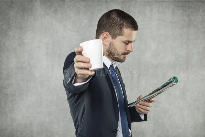 Affärsman som dricker kaffe och läsning tidningen arkivbilder