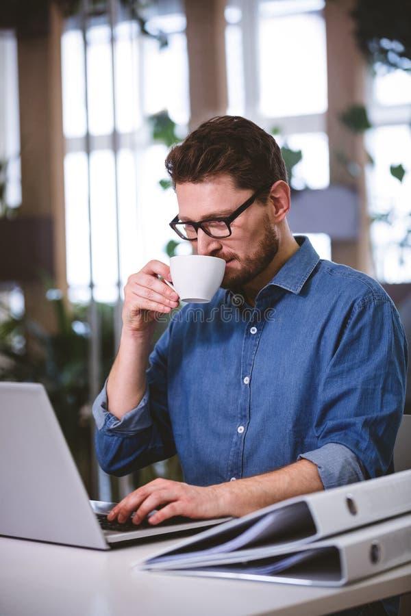 Affärsman som dricker kaffe på det idérika kontoret royaltyfria bilder
