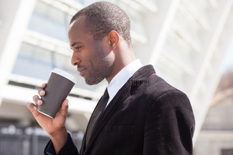 Affärsman som dricker kaffe under en lunch royaltyfria foton