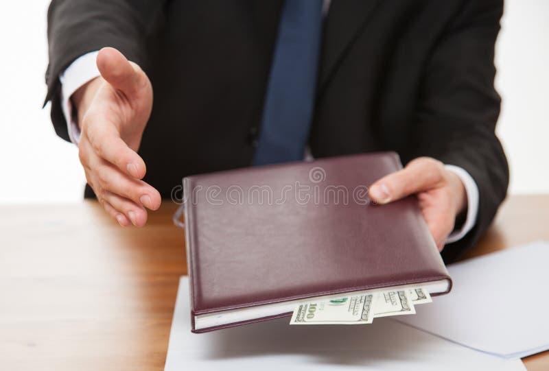 Affärsman som erbjuder en handskakning och en muta arkivbild