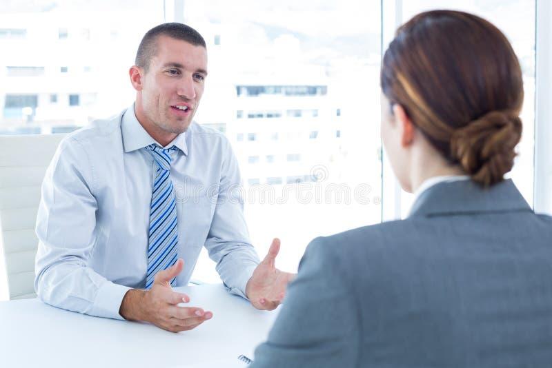 Affärsman som för en intervju med affärskvinnan arkivbild