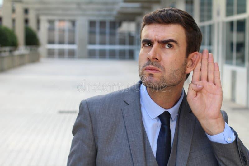 Affärsman som försöker att höra ett skvaller royaltyfri foto