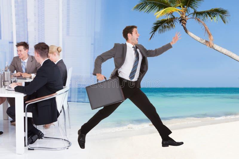 Affärsman som flyr från konferensmöte in mot stranden royaltyfria foton