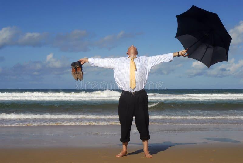 Affärsman som flyr till en strandsemester, utsträckta armar, avgånglyckabegrepp royaltyfri bild