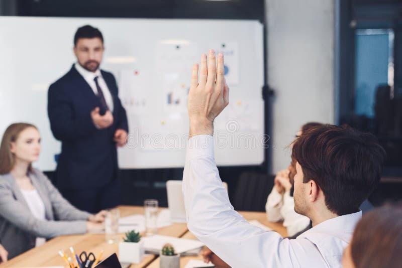Affärsman som frågar fråga till högtalaren på presentationen royaltyfri foto