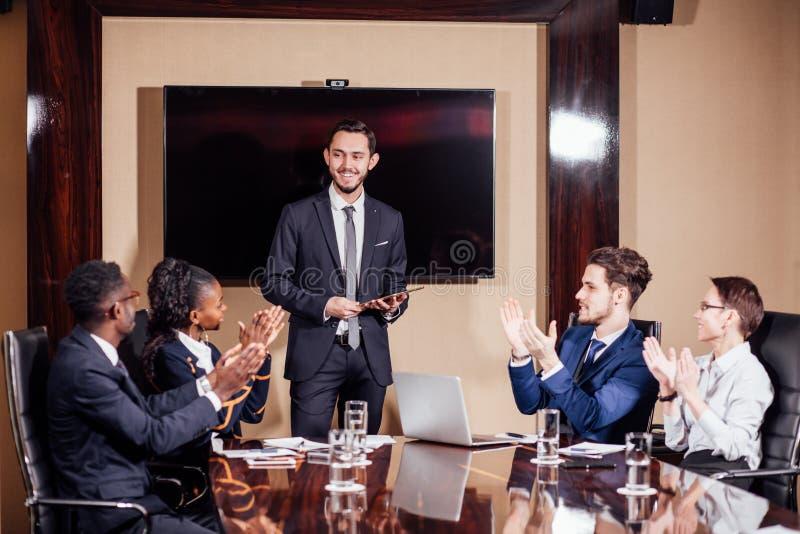 Affärsman som framlägger till kollegor på ett möte arkivfoto