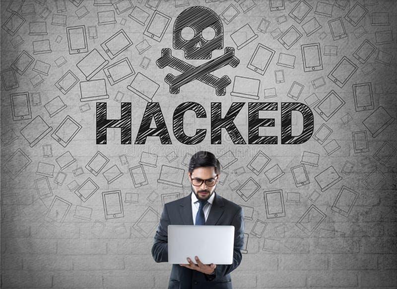 Affärsman som framme använder bärbara datorn av det hackade symbolet royaltyfria bilder