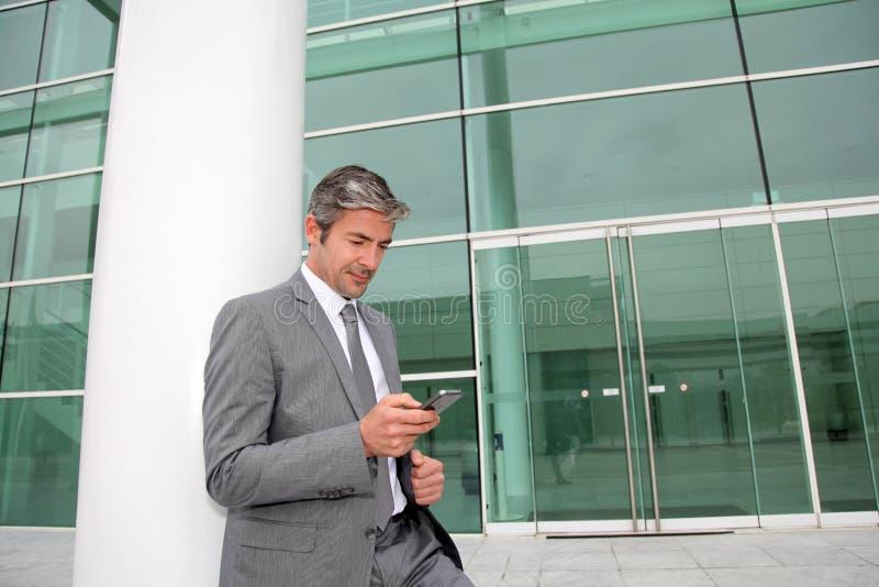 Affärsman som framme använder smartphonen av kontorsbyggnad arkivfoton