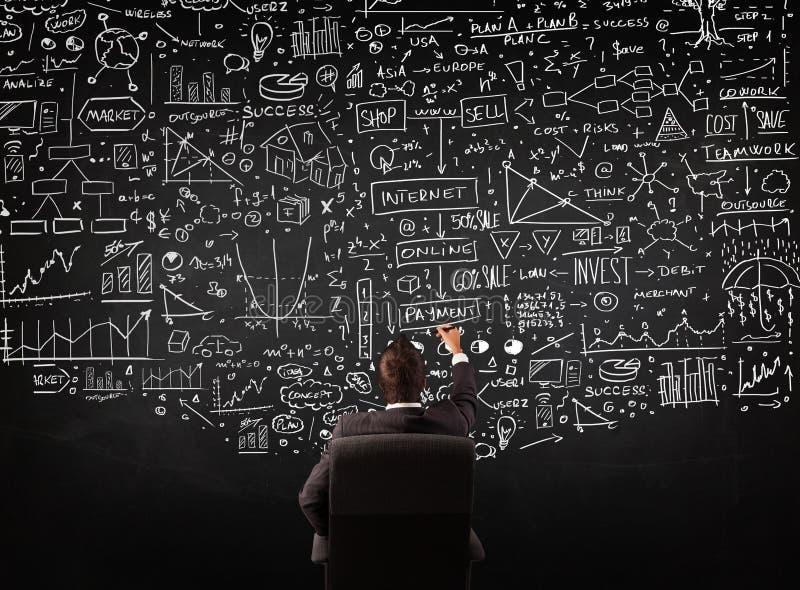 Affärsman som framme sitter av en svart tavla med diagram royaltyfri foto