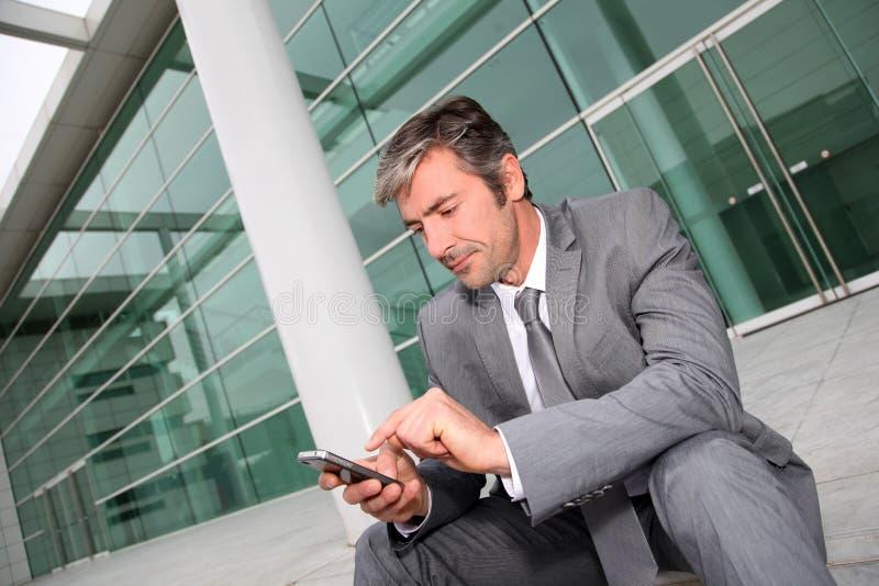 Affärsman som framme sitter av modern byggnad och använder smartphonen arkivfoton