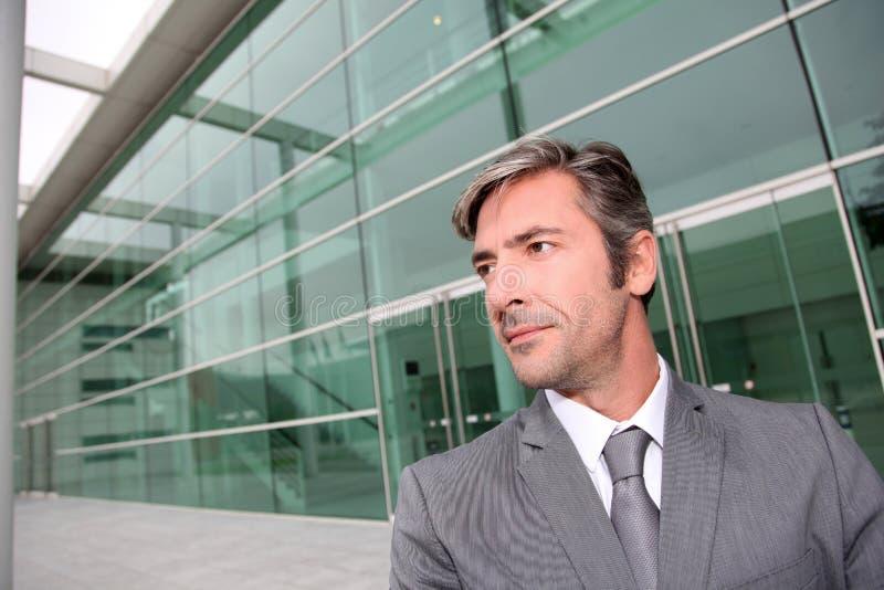 Affärsman som framme står av kontorsbyggnad arkivbilder