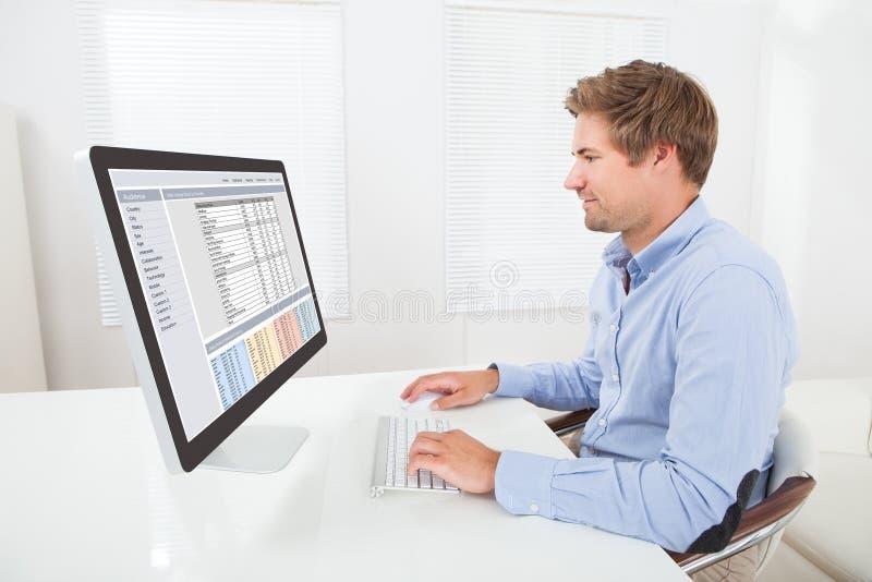 Affärsman som fungerar på datoren royaltyfri bild