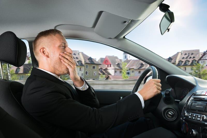 Affärsman som gäspar, medan köra bilen royaltyfri fotografi
