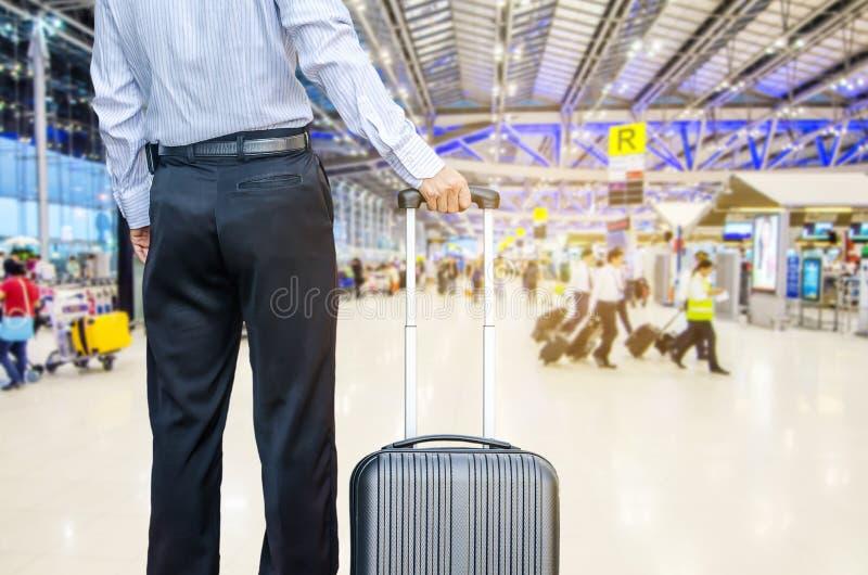 Affärsman som går lopppåsen vid en internationell flygplats royaltyfri foto