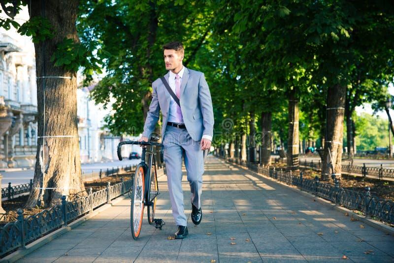 Affärsman som går med cykeln arkivbilder