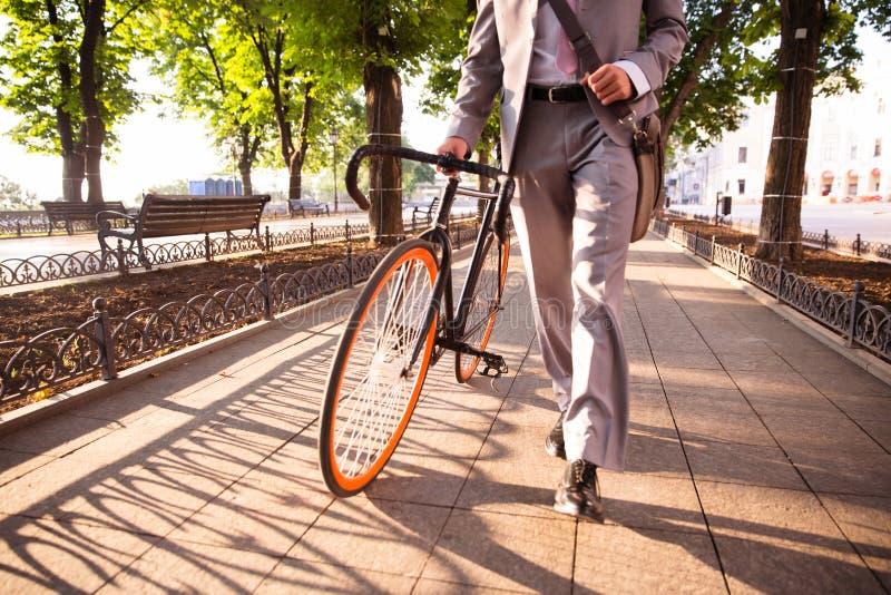 Affärsman som går med cykeln royaltyfri bild