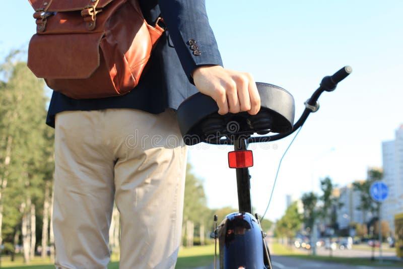 Affärsman som går med cykeln i gata efter arbete arkivbilder