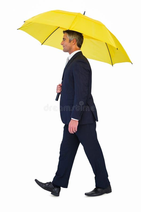 Affärsman som går och rymmer det gula paraplyet arkivfoton