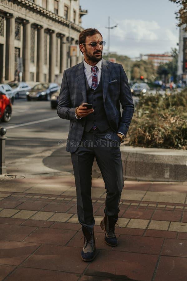 Affärsman som går och rymmer mobiltelefonen royaltyfri bild