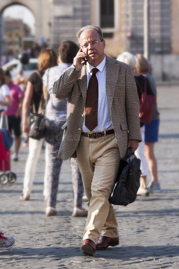 Affärsman som går och talar på telefonen royaltyfri foto
