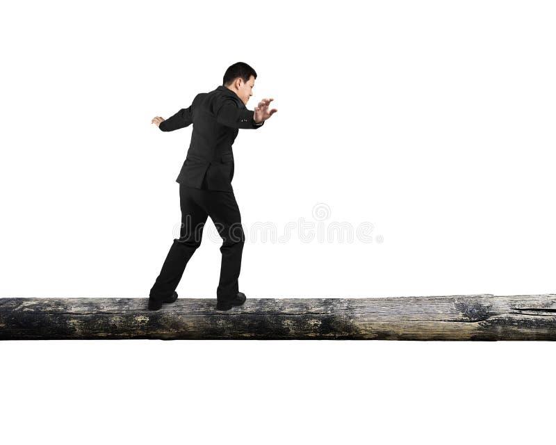 Affärsman som går på trädstammen royaltyfri bild