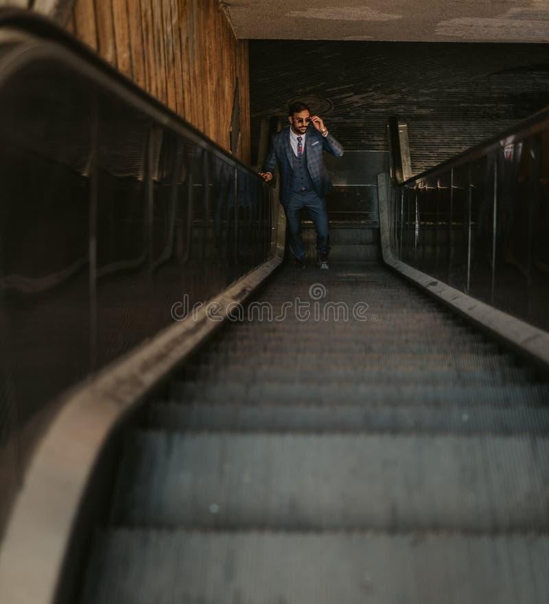 Affärsman som går upp på rulltrappan, medan rymma solglasögon arkivfoto