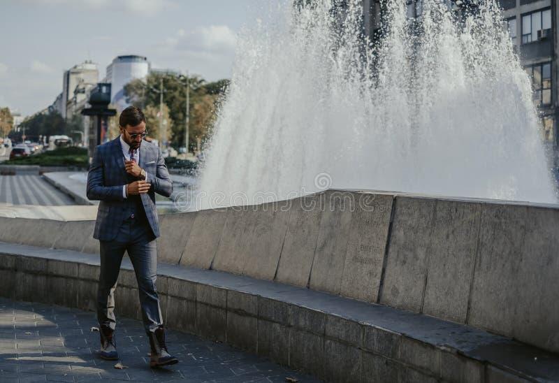 Affärsman som går vid springbrunnen i staden royaltyfri foto