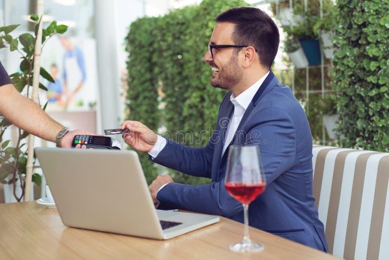Affärsman som gör contactless kortbetalning i ett kafé royaltyfri bild