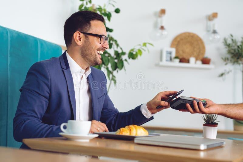 Affärsman som gör contactless kortbetalning i ett kafé royaltyfria foton