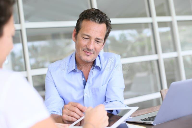 Affärsman som gör ett avtal med hans klienter fotografering för bildbyråer