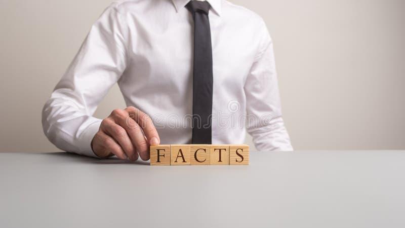 Affärsman som gör fakta för ett tecken med träkuber fotografering för bildbyråer