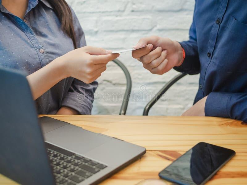 Affärsman som ger affärskortet till affärskvinnan i kontoret Affärspartnerbegrepp arkivbilder