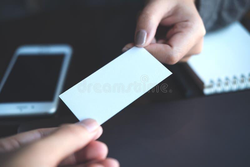 Affärsman som ger affärskortet till affärskvinnan med mobiltelefonen och anteckningsboken royaltyfri fotografi