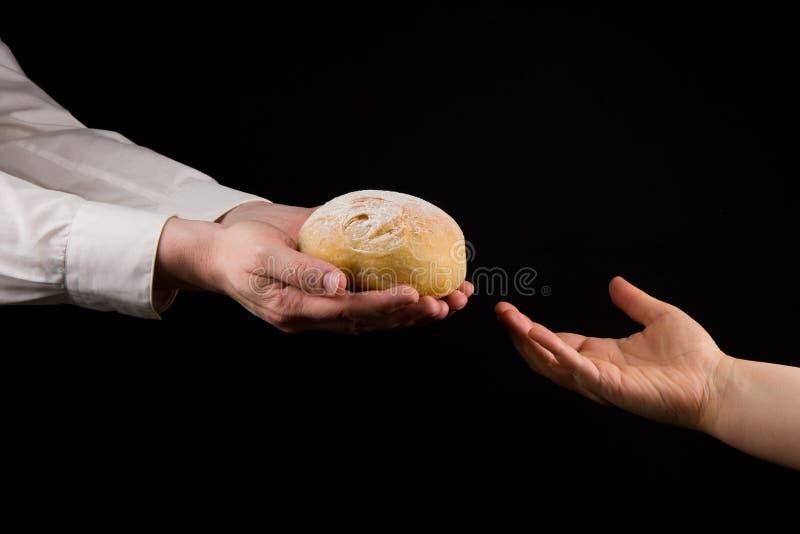 Affärsman som ger bröd till en kvinna Begrepp för portionhand arkivfoto