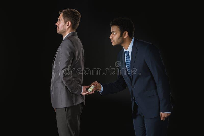 Affärsman som ger pengar och muter affärspartnern royaltyfri bild