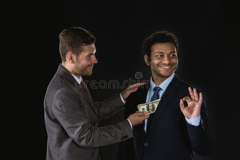 Affärsman som ger pengar och muter affärspartnern royaltyfri fotografi