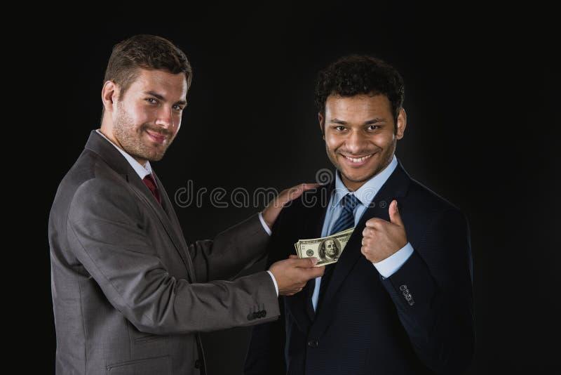 Affärsman som ger pengar och muter affärspartnern arkivbild